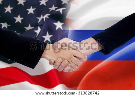 Two workers shaking hands after good negotiation in front of the russian and american flags