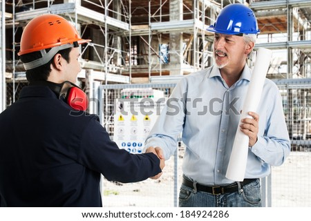 Two workers shaking hands in a construction site - stock photo