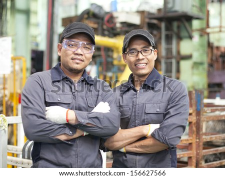Two workers standing in factory - stock photo
