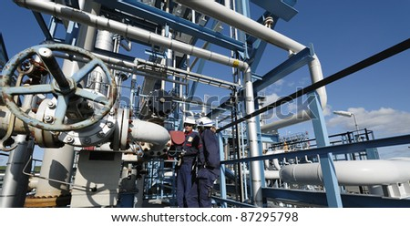 two workers standing on a construction inside refinery - stock photo