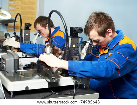 two workers technicians checking detail quality in tool workshop - stock photo
