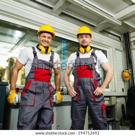Two workers wearing safety hat in a factory control room - stock photo