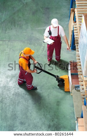 Two workers with fork pallet truck stacker in warehouse loading furniture panels - stock photo