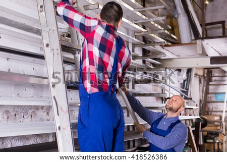Two workmen in uniform choosing PVC window profile at stand - stock photo