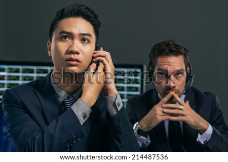 Two worried business brokers looking at the electronic stock exchange board - stock photo