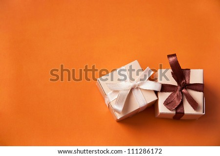 Two wrapped gift boxes with colorful satin ribbons and bows on orange background in studio. Focus on a bow - stock photo