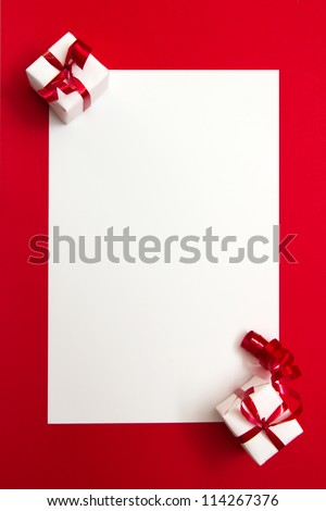 Two wrapped gifts represent christmas theme, with a blank white card for text - stock photo