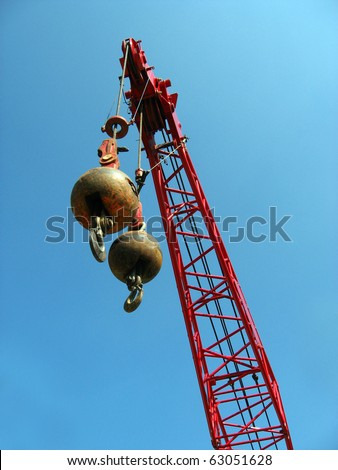 Two wrecking balls suspended from a red crane, high above the ground, against a blue sky background. - stock photo