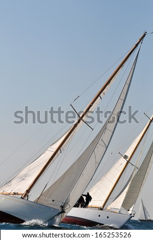 Two yachts engaged in a sailing race with another in background - stock photo