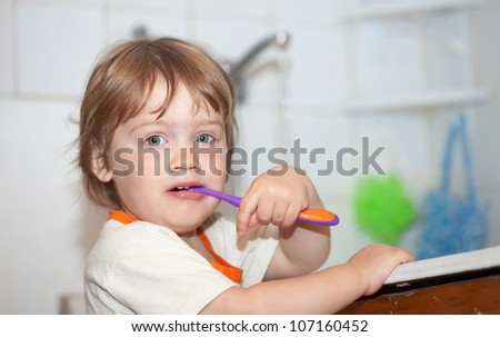 Two-year baby gir brushes her teeth - stock photo
