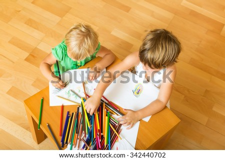 Two year children sketching on paper at home - stock photo