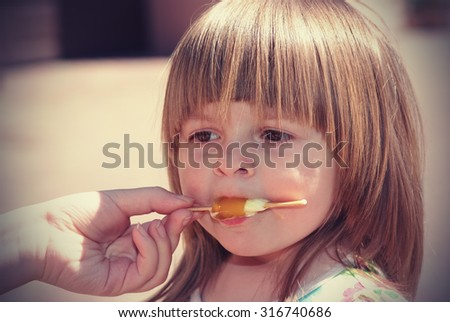 Two-year girl in a colorful dress eats ice cream outdoors - stock photo