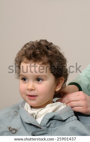 Two year old girl gets haircut at home (mom's hands are putting the finishing touches) - stock photo