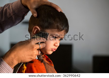 two year old kid having a haircut  with wet eyes after crying early morning with golden light falling on his face - stock photo