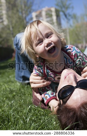 two years aged blonde happy baby colored shirt hugging with brunette woman mother with black sunglasses lying on green grass lawn - stock photo