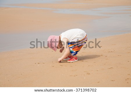 two years blonde baby with pink hat white shirt and colorful trousers looking for, picking and collecting sea shells in golden sand beach seaside with ocean water - stock photo