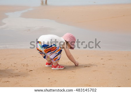 two years blonde baby with pink hat white shirt and colorful trousers looking for, picking and collecting sea shells in golden sand beach seaside with ocean water