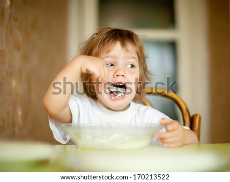 two-years child himself eats from plate  with spoon - stock photo