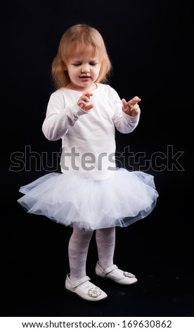 Two years old baby girl wearing white suit and crossing fingers at black background.