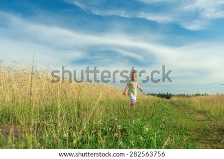 Two years old blonde toddler girl is walking by foot on dirt road among cereal field - stock photo