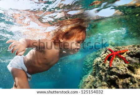 Two years old boy diving underwater to see red starfish - stock photo