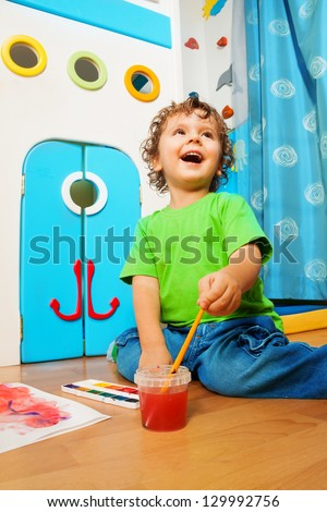 Two years old boy painting with laughing expression dipping paintbrush into water bucket - stock photo