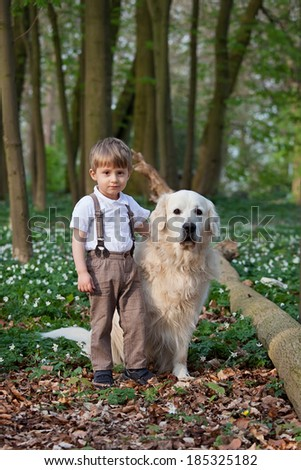 Two years old boy with his dog outdoor portrait - stock photo