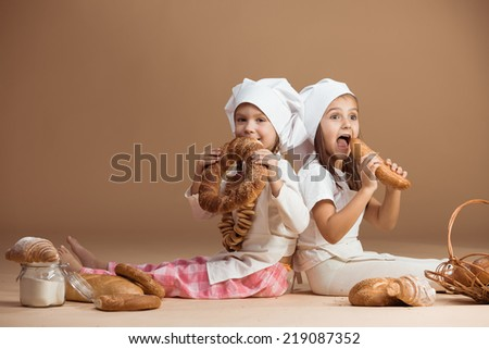 Two 5 years old girl bakers eating bakery products, studio shot - stock photo