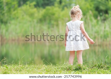 Two years old girl in light summer dress near green forest pond - stock photo