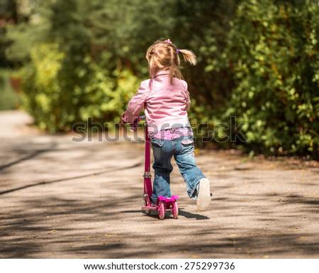 Two years old girl riding her scooter on the park. back  view - stock photo