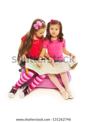 Two 6-7 years old girls sitting on suitcase with map preparing to travel, isolated on white