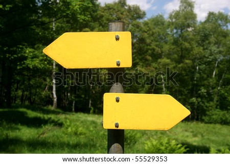 Two yellow arrow signs, one right, one left direction in front of trees - stock photo