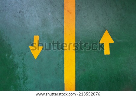 Two yellow arrows forward backward on green asphalt pedestrian road. - stock photo