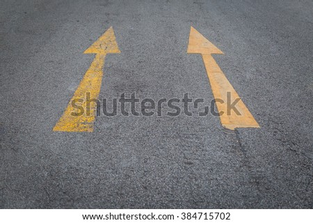 Two yellow arrows old and new  directionon asphalt road background