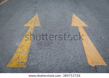Two yellow arrows old and new  directionon asphalt road background - stock photo