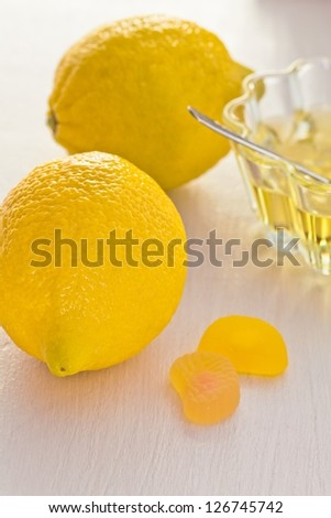Two yellow lemon and honey glass cup on a white background with candy - stock photo