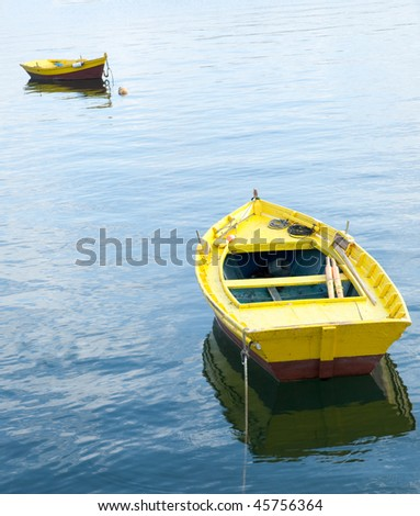 Two yellow rowing boats on the sea - stock photo