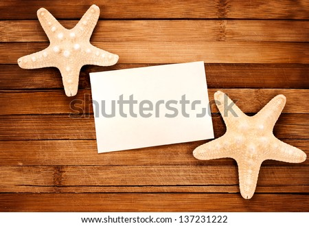 Two yellow seashells on a wooden background and paper card.
