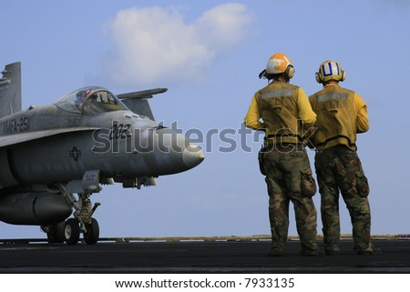 "Two ""Yellow Shirt"" Aircraft Directors Stand in Front of an F/A-18C Hornet on the Nuclear Aircraft Carrier, USS Enterprise - stock photo"