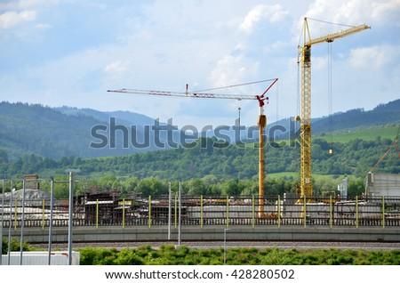 Two yellow tower cranes on construction site working on highway. Railway in foreground. - stock photo