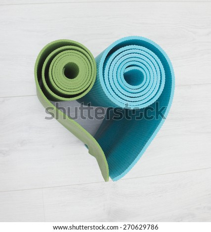 two yoga mats stacked in the shape of heart green and blue colors - stock photo