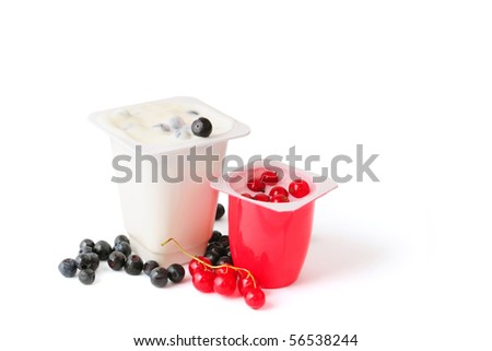 Two yoghurts with blueberries and red currants isolated on white - stock photo