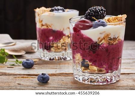 Two yogurt desserts with berries and muesli. - stock photo