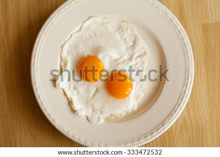 Two yolks of eggs on the white plate. - stock photo
