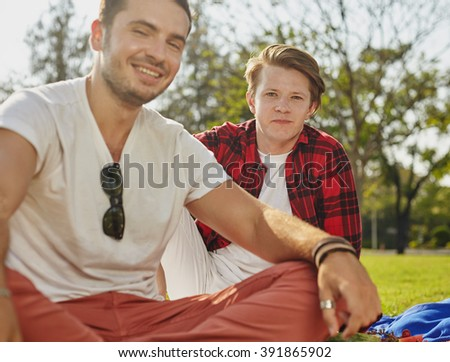 Two yong guy sitting on the grass in the park on the picnic