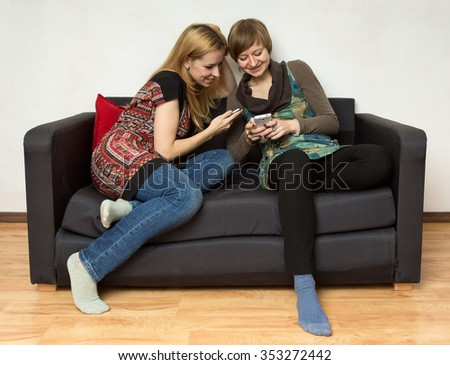 Two yong women in bright dresses are sitting on the black sofa with cellphones - stock photo