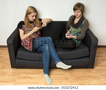 Two yong women in bright dresses are sitting on the black sofa with cellphones, looking at the screens - stock photo