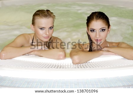 two young adult beautiful and attractive sensuality brunette girls in jacuzzi - stock photo