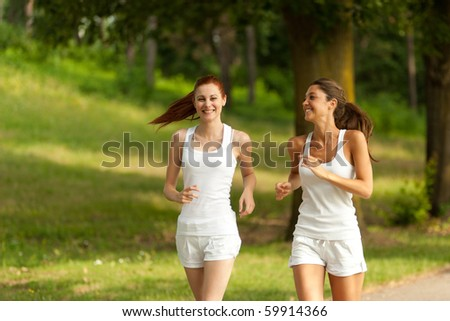 two young adult woman running in a park - stock photo