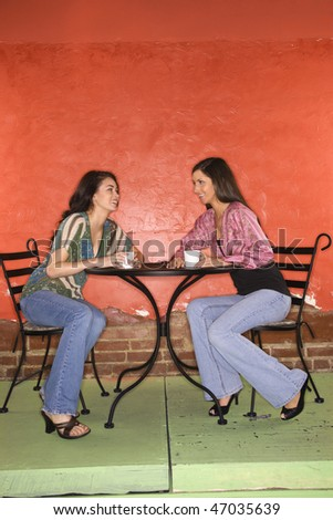 Two young adult women sitting in a cafe, having coffee and talking. Vertical shot.